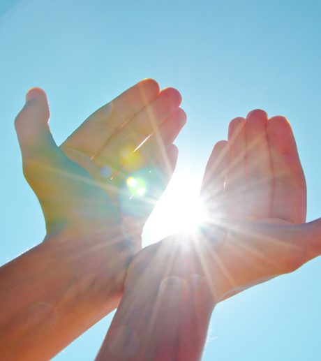 Hands holding the sun with the blue sky background.